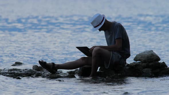 Thumbnail for Man Sitting on the Rock on Seaside with Notebook at Dusk. Freelancer Working on the Nature. Hipster