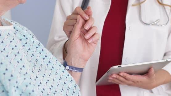 Thumbnail for Japanese Doctor holding hand of elderly female patient