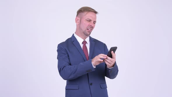 Cover Image for Stressed Blonde Businessman Using Phone and Getting Bad News