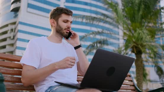 Cover Image for A Man in a White T-shirt with a Laptop Talking on the Phone in the Summer on the Bench