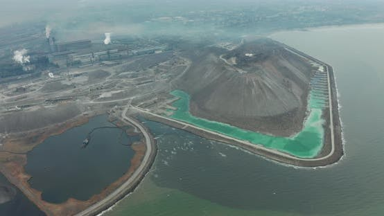 Cover Image for Aerial View. Drone Flying Forward Over a Polluted Sea with Destroyed Ecosystem. Slag Dump Poisoning