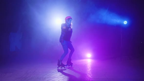Happy and Cheerful Girl, a Professional Roller in a Helmet and Protection, Dances and Performs U