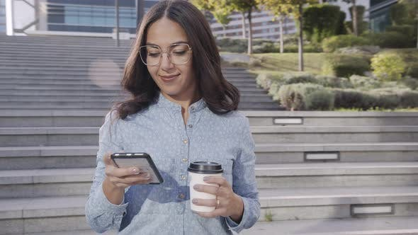 Cover Image for Smiling Hispanic Woman with Coffee To Go Using Smartphone on Stairs