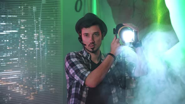 Filmmaker Looking at Camera While Using a Fresnel Lamp