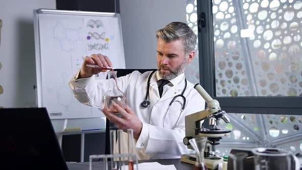 Thumbnail for Male Doctor Doing Chemical Experiments with Liquids in Test Tube and Flask in Medical Lab