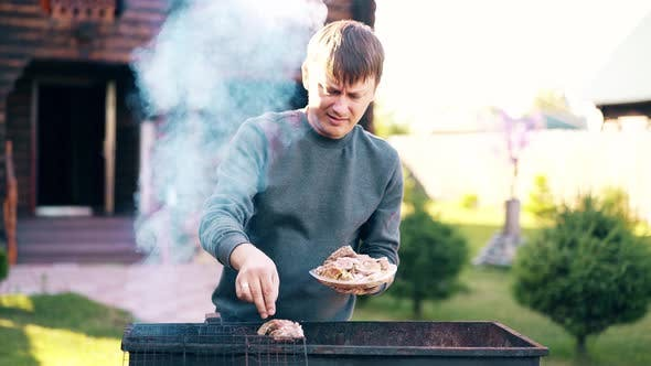 Thumbnail for Young Man Stands on the Background of a Summer House Lays Marinated Pork on a Barbecue Grill