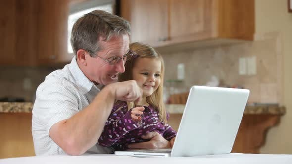 Grandfather and granddaughter on laptop
