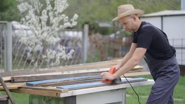 Thumbnail for Der Mann im Hut in seiner Hütte. Ein Mann arbeitet als Elektrobaum-Bank. Wir sind streng mit Alten