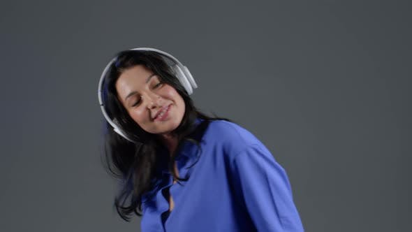 Thumbnail for Attractive European Adult Woman with Long Hair Dancing with Headphones on Grey Studio Background.