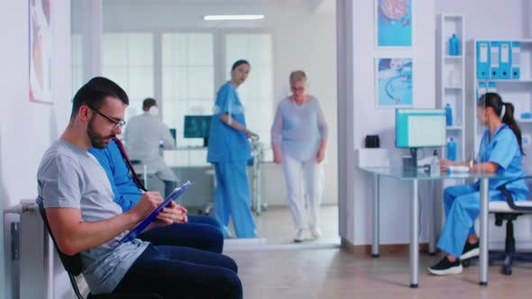 Cover Image for Man Filling Paperwork in Hospital Waiting Area