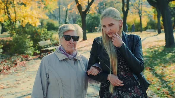 Old Woman Walking Together with Cheerful Blonde Girl in Autumn Park