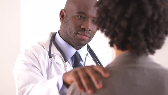 Black doctor talking to patient
