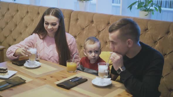 Happy Family Taste Beverages in Restaurant with Pot Plant