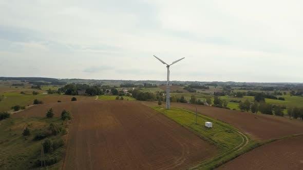 Thumbnail for Luftaufnahme einer einzelnen Windenergieanlage, die schnell rotiert. Sommerlandschaft mit landwirtschaftlichen Feldern