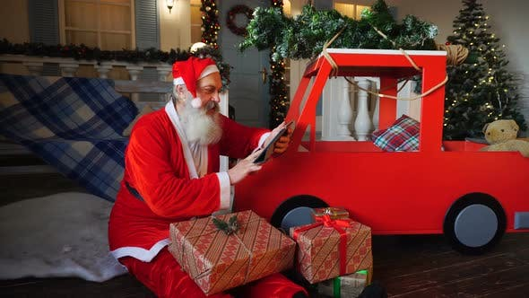 Thumbnail for Santa Claus Makes List of Presents Using Tablet.