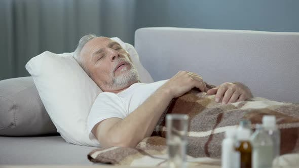 Thumbnail for Old ill male sleeping on sofa at home, medicaments standing on the table