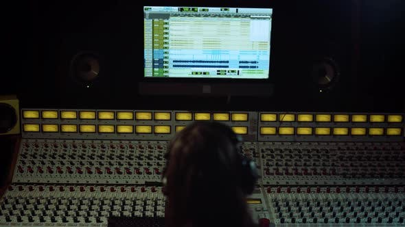 Thumbnail for Unrecognizable Sound Engineer Touching Soundboard in Recording Music