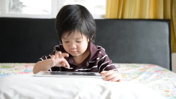 Asian Baby Using Tablet On Bed