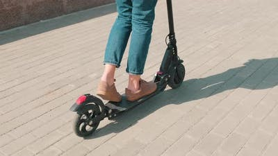 Woman On E-Scooter In City Centre