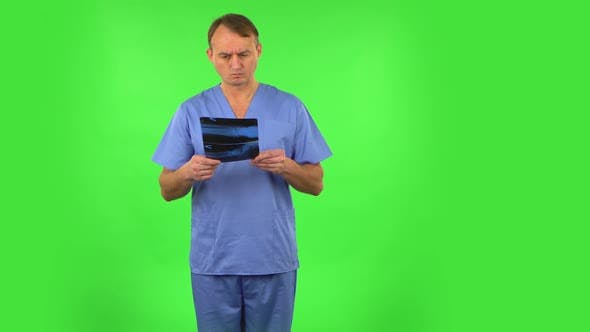 Thumbnail for Male Doctor in Blue Coat Reviewing X-ray Pointing on Snapshot. Green Screen