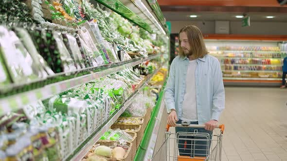 Vegetarianism Young Man Chooses and Buys Vegetables in a Hypermarket Buying Healthy Food in an