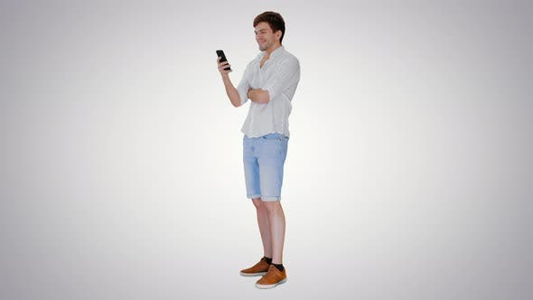 Handsome Young Man Using His Smartphone and Laughing on Gradient Background
