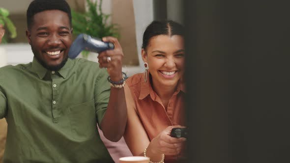 Laughing Biracial Couple Playing Video Games Together