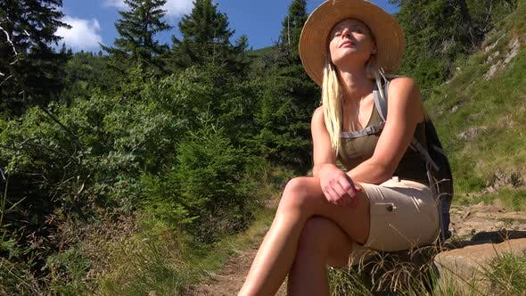 Thumbnail for A Young Beautiful Woman Sits on a Rock on a Hill on a Sunny Day and Looks Around - View From Below