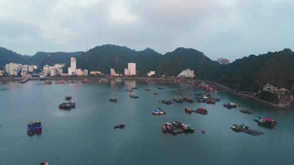 Aerial: Vietnam Cat Ba bay at twilight with floating fishing boats on sea, city skyline