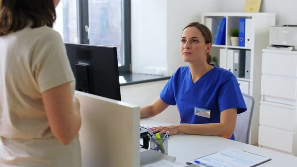 Doctor with Computer and Patient at Hospital