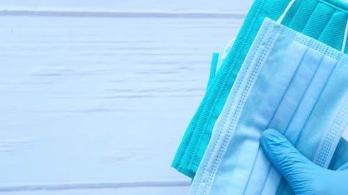 Hand in Schutzhandschuhe mit Schutzmaske und Desinfektionsmittel