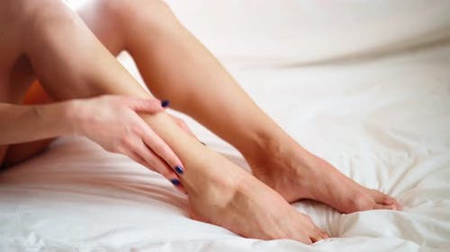 Woman Applying Moisturizer Cream on Her Slim Legs
