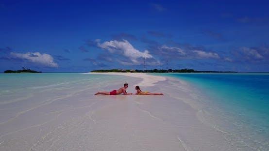 Happy boy and girl on romantic honeymoon enjoy luxury on beach on sunny white sandy background 4K