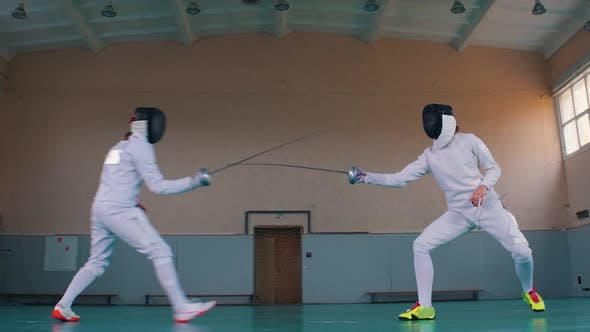 Thumbnail for Two Young Women Having an Active Fencing Training in the School Gym