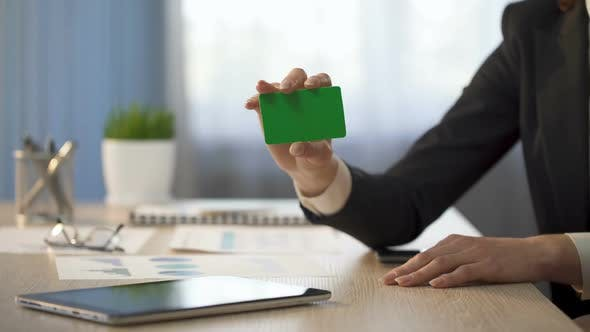 Cover Image for Businesswoman Showing Business Card With Green Field, Banking Services Ad