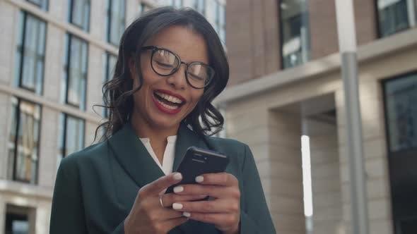 Happy Businesswoman Using Smartphone Outdoors
