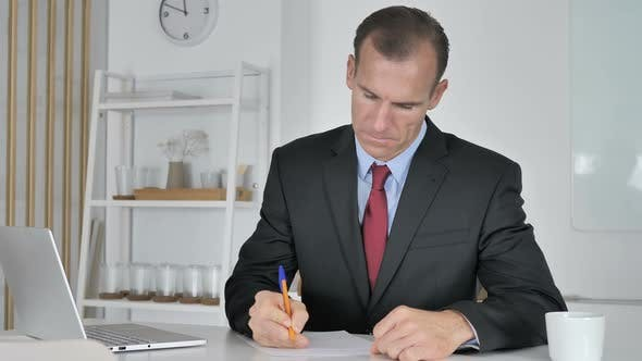 Thumbnail for Middle Aged Businessman Writing Documents in Office