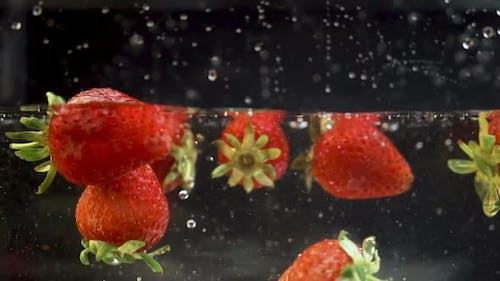 A couple of ripe strawberries getting into a liquid