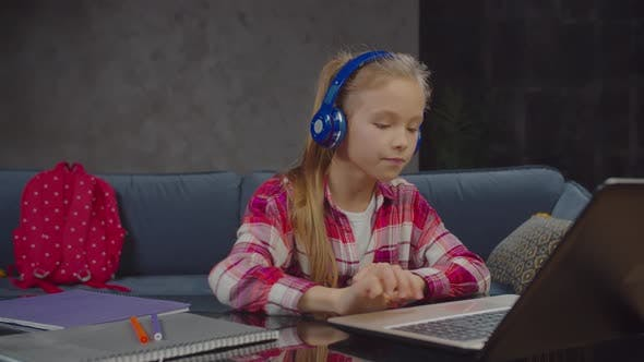 Thumbnail for Cute Schoolgirl Enjoying Music Online at Home
