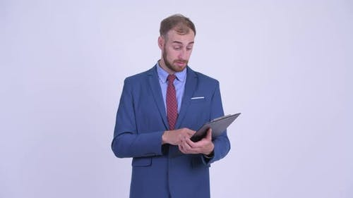 Happy Bearded Businessman Reading on Clipboard and Giving Thumbs Up