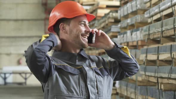Thumbnail for Happy Factory Worker in a Hardhat Smiling Talking on the Phone