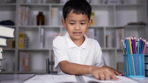 A boy practicing reading at desk.