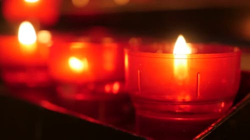 Lit of prayer red cups of Christian catholic votive candles in candle rack 4K 2160p 30fps UltraHD fo