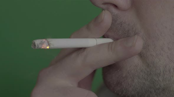 Thumbnail for Cigarette in the Mouth of a Smoker. Close-up. Chroma Key. Green Background.