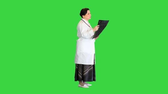 Senior Female Radiologist Examining Brain Scan Mri on a Green Screen Chroma Key