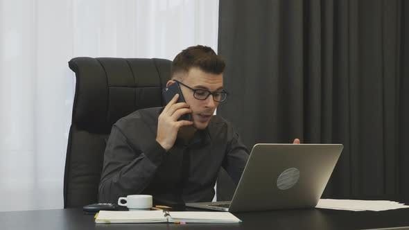 Thumbnail for Angry male boss talking on phone and screaming sitting in his modern office. Business concept