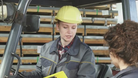 Thumbnail for Young Female Fatory Worker Operating Forklift at the Storage Talking To Her Colleague