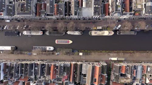 Canal Boat Tour in Amsterdam Amongst Riverside Houses Bird's Eye View