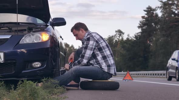 Thumbnail for Guy Changing a Tire Outdoors