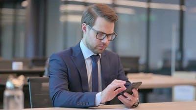 Businessman Browsing Internet on Smartphone in Office